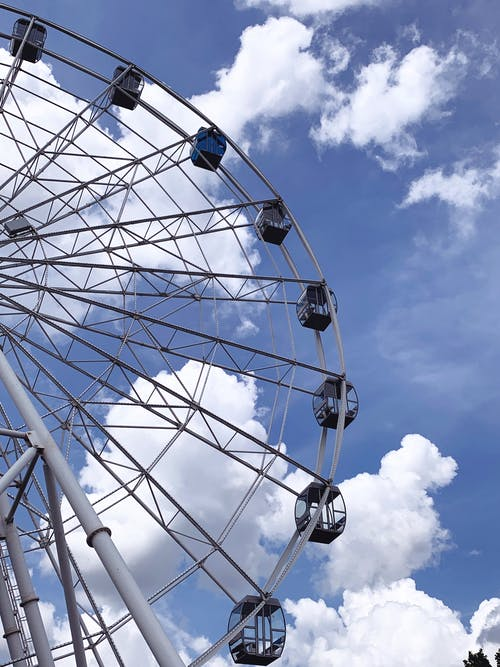 From below of Ferris wheel amusement ride for observe from height against clouds on blue sky