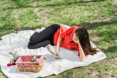 Woman Lying Down on Picnic Blanket while Reading a Book