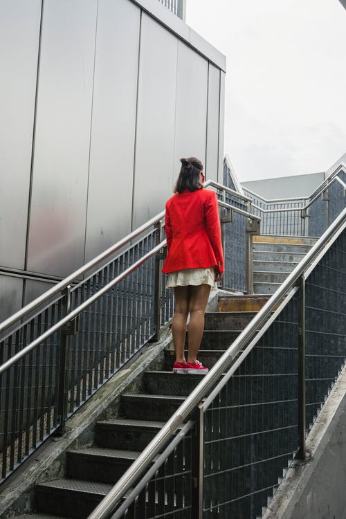 Woman in Red Suit Climbing the Stairs