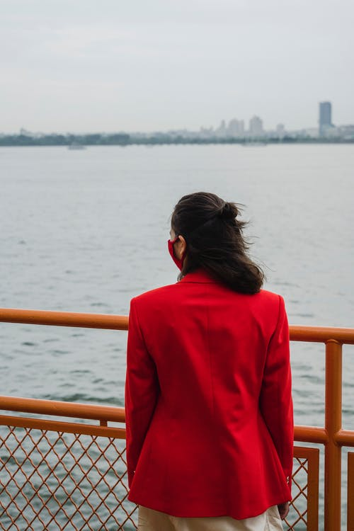 Woman in Red Suit Standing by the Metal Railings