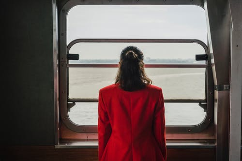 Woman in Red Long Sleeve Shirt Standing in Front of Brown Wooden Window