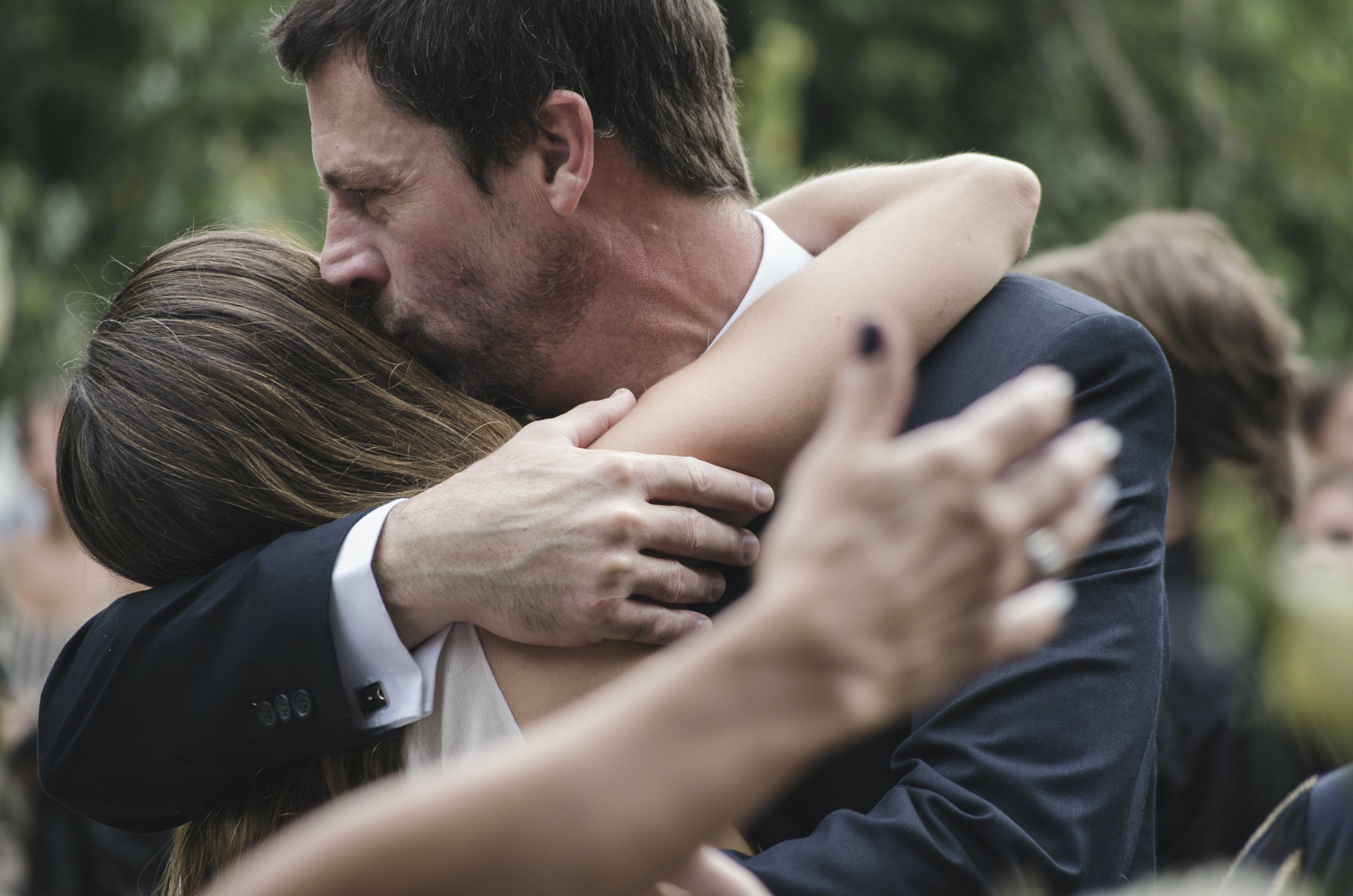 Man and Woman Hugging While Man Kissing Woman's Head