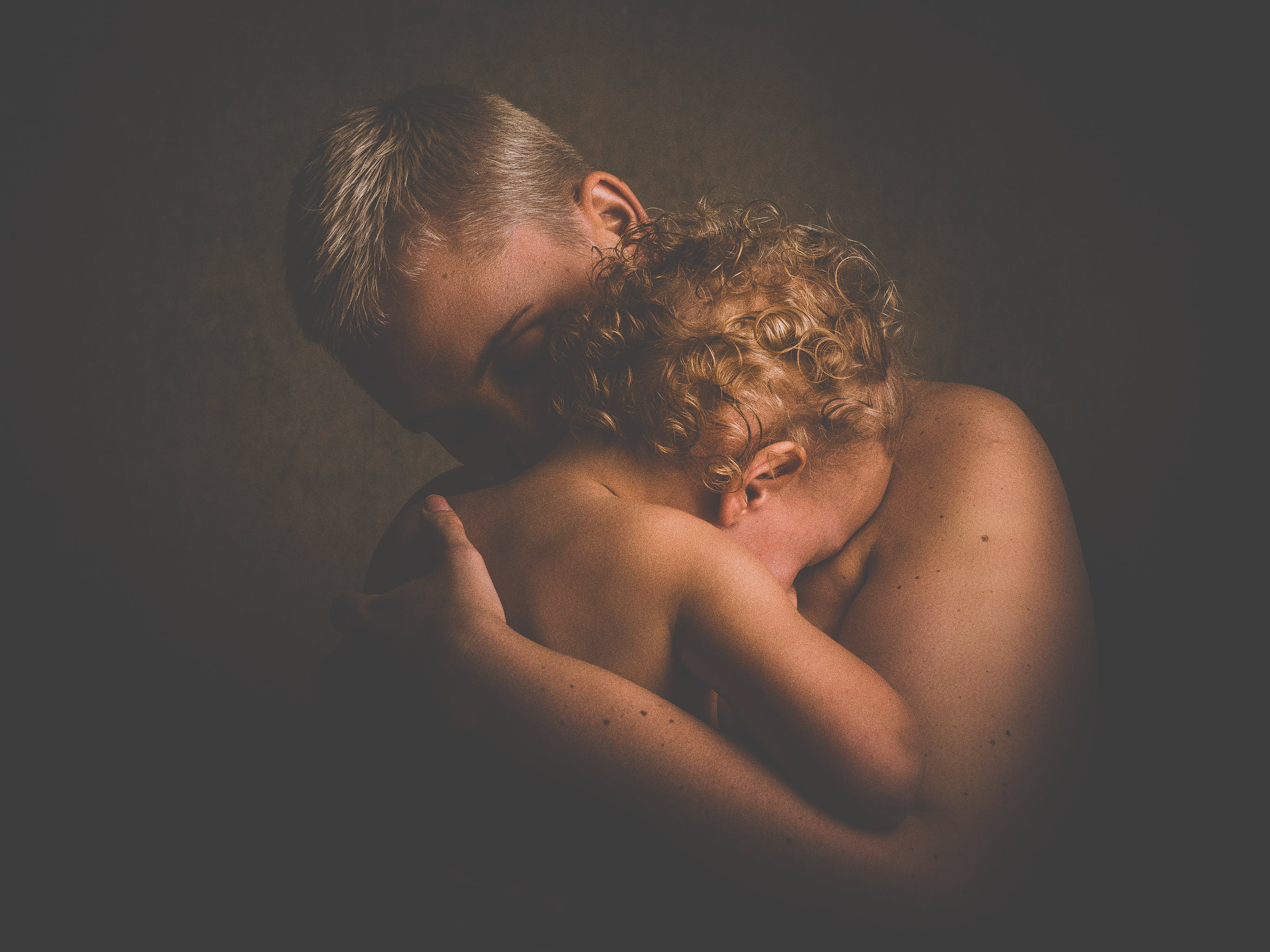 Photo of Topless Person Carrying Curly Haired Child