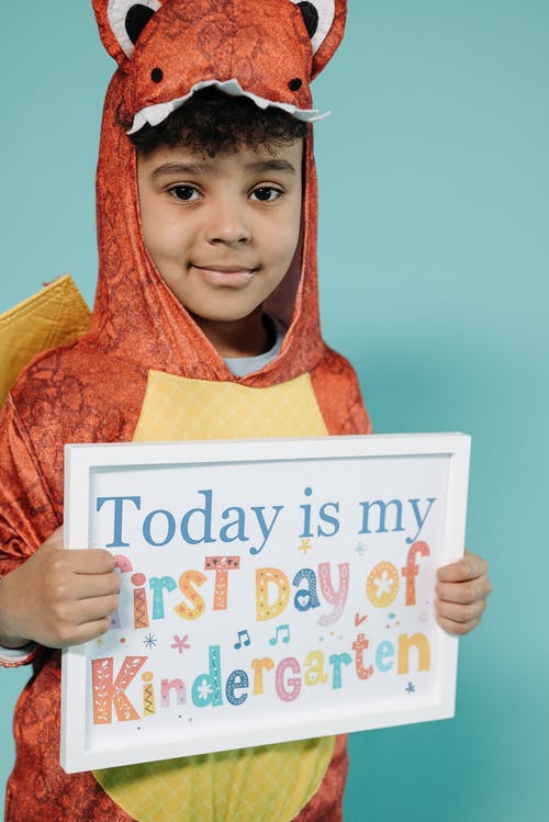 Boy in Orange and Yellow Animal Costume Holding White Picture Frame
