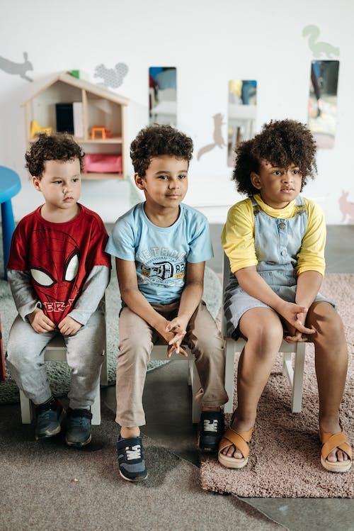 Children Sitting on White Chair