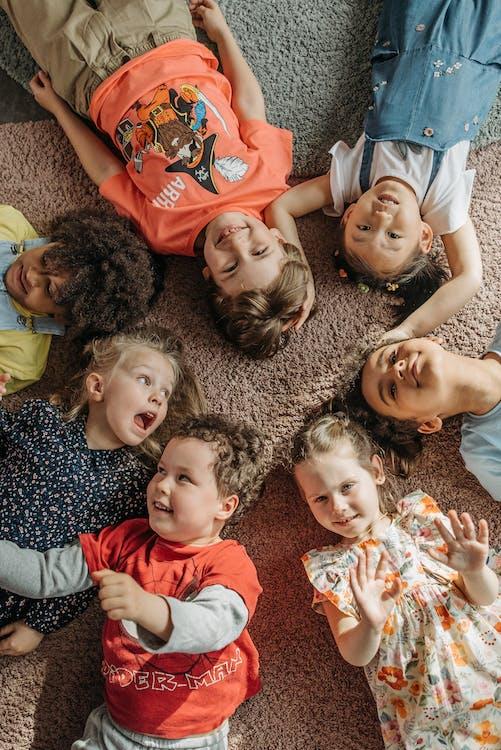 3 Children Lying on Brown Carpet