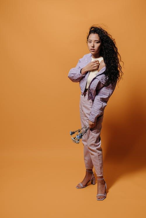 Woman in Purple Jacket Standing on Orange Background