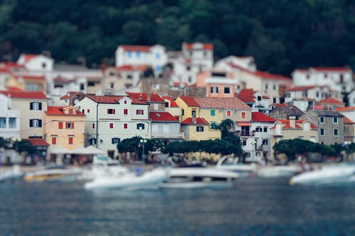 Tilt Shift Lens Photography of Red Roof House Near the Body of Water