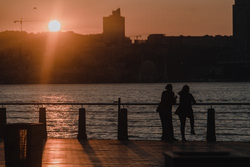 Silhouette of Couple Standing on Dock during Sunset