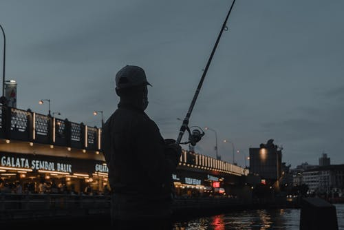 Silhouette of Man Fishing on Sea during Night Time