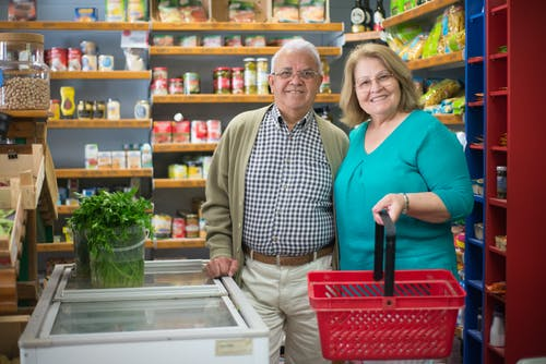 Smiling Elderly Couple Buying Groceries