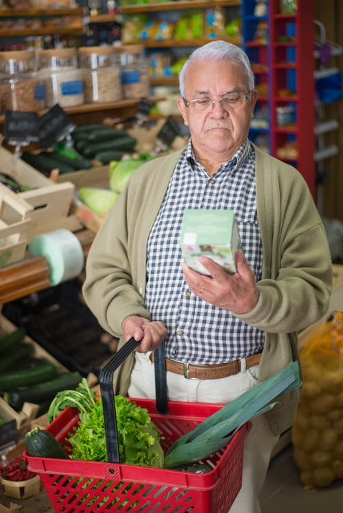 Man in Green Long Sleeve Shirt Holding Green and White Plastic Container