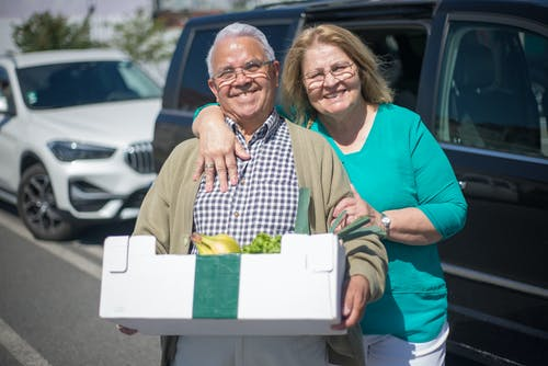 Smiling Elderly Couple Holding a Box of Groceries