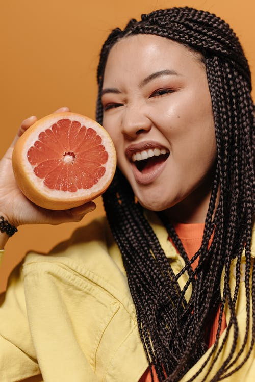 Woman Smiling while Holding a Pomelo