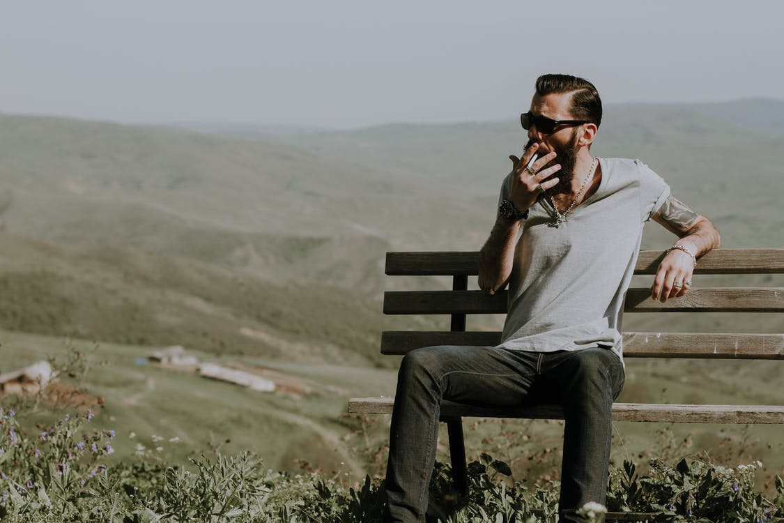 Photo of a Man Sitting on Wooden Bench