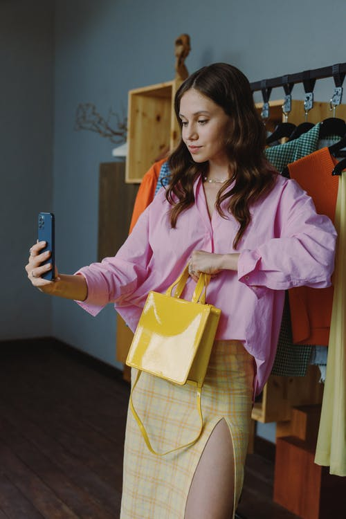 Woman in Pink Robe Holding Blue Smartphone