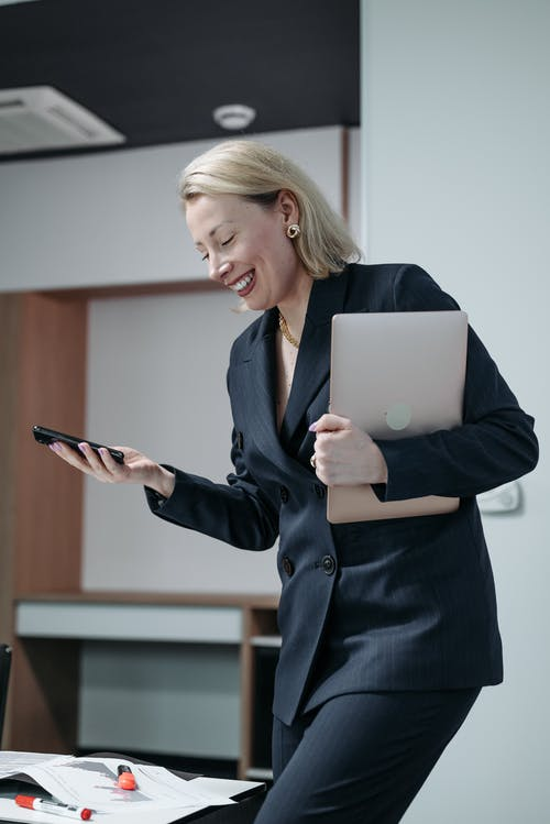 Woman in Black Blazer Holding a Laptop while Using a Smartphone