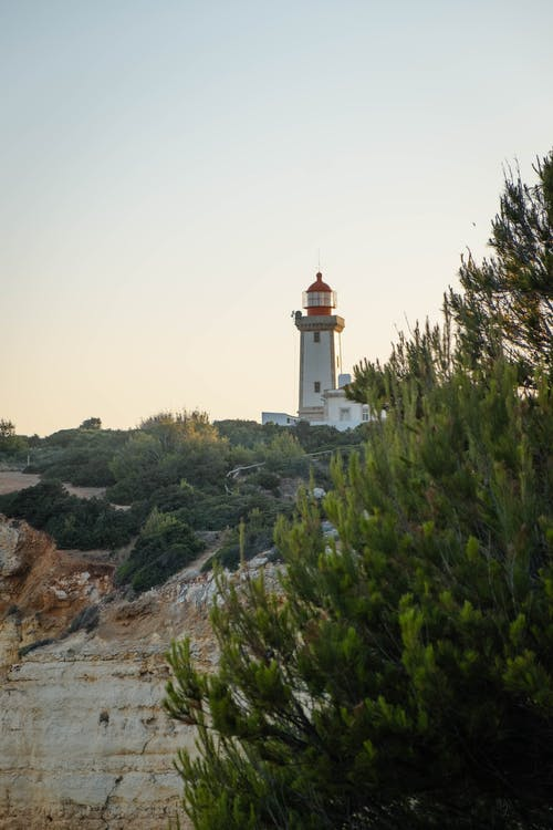 White and Brown Lighthouse on Top of Hill