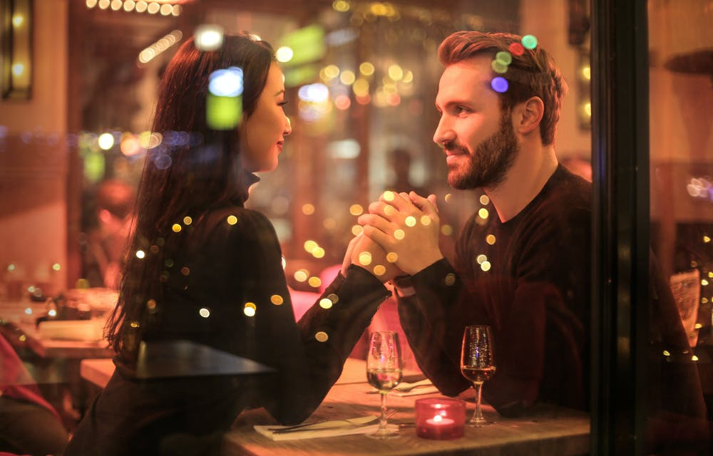 Couple holding each other hands at the restaurant. | Photo: Pexels