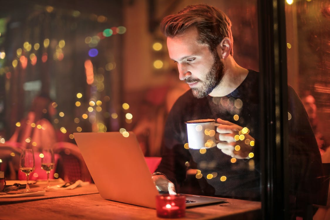 Man Holding Mug in Front of Laptop fashion blogger