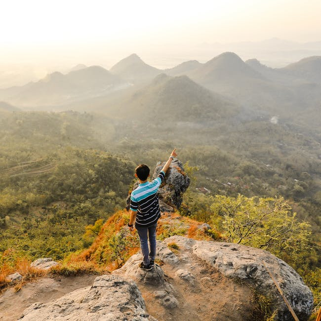 Photo of man standing on rock mountain pointing out mountain