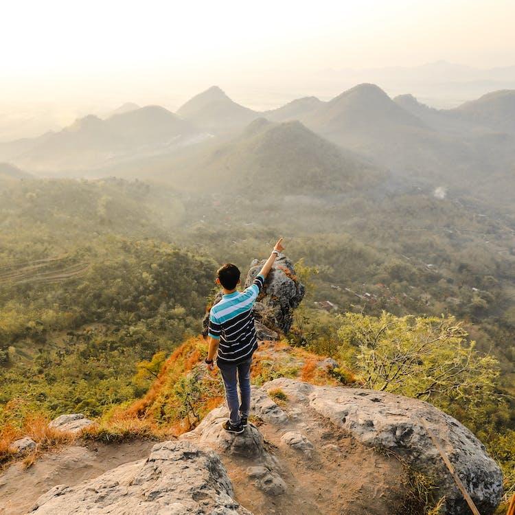 Фотография человека, стоящего на скалистой горе, указывая на гору