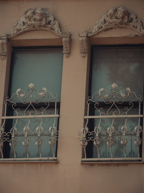 Low angle of aged residential building with forged metal fence and stucco ornament