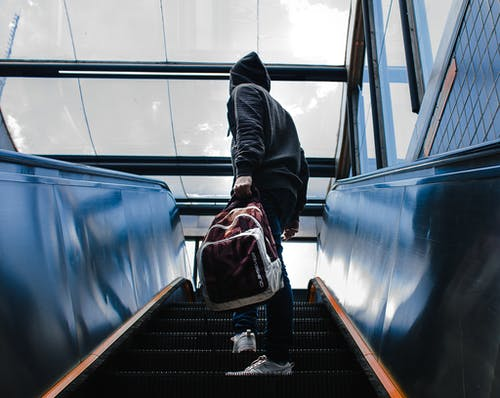 Person Wearing Black Hooded Jacket Standing on Escalator While Holding Backpack