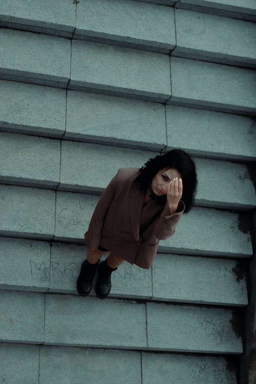Woman in Red Long Sleeve Shirt and Black Pants Standing on Gray Concrete Stairs