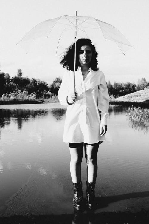 Woman in White Coat Holding Umbrella Standing on River