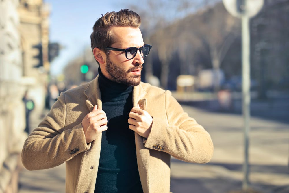 Man wearing eyeglasses and brown jacket outside of the house.   Photo: Pexels
