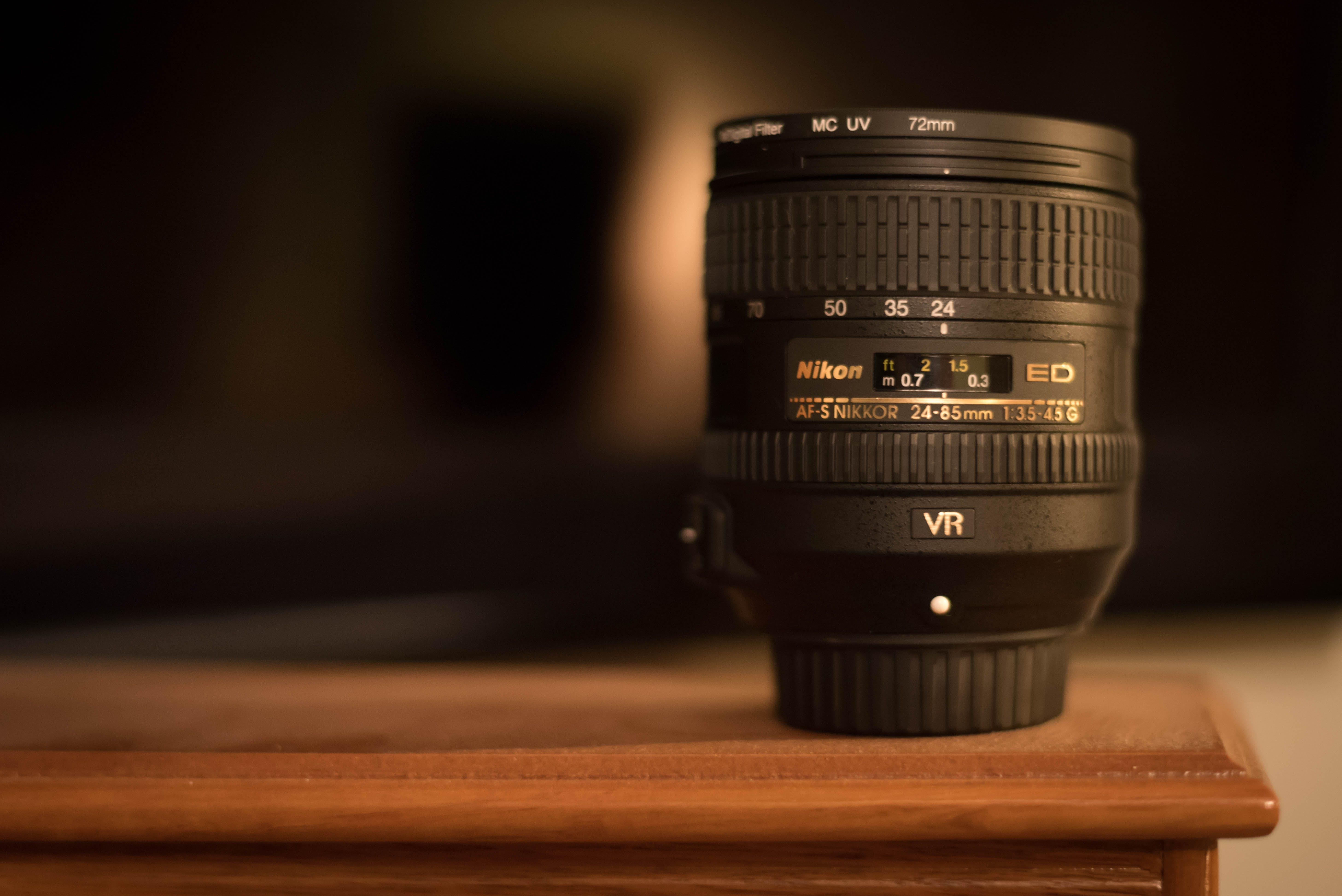 Black Nikon Dslr Camera Lens on Brown Surface