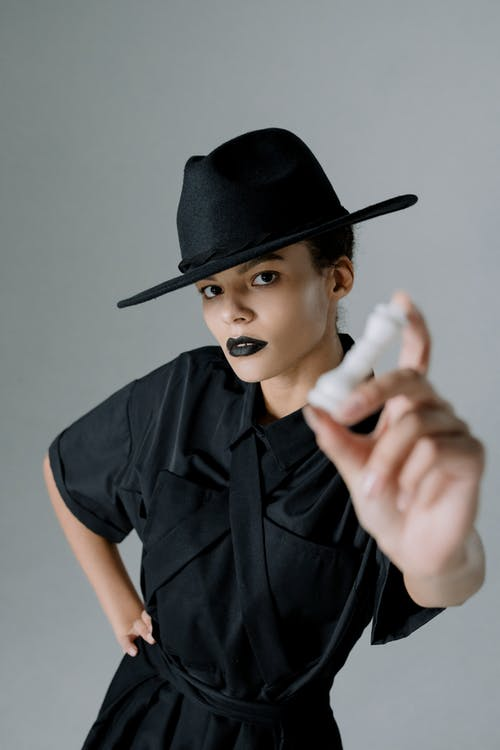 A Woman in a Black Dress and Black Hat Holding a Chess Piece
