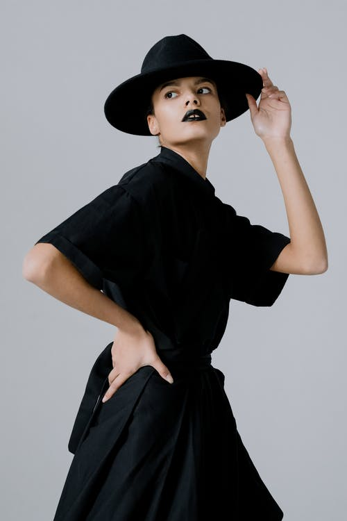 A Woman in a Black Dress and Black Hat Posing