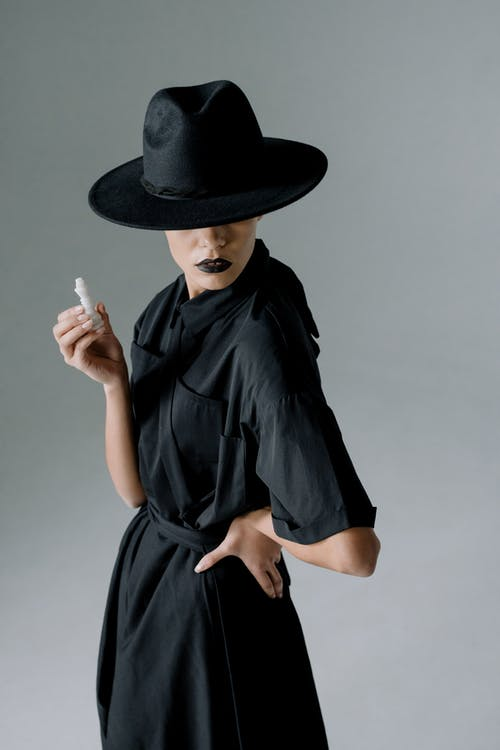 A Person in a Black Dress and Black Hat Holding a Chess Piece