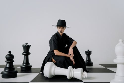 Man in Black Shirt and White Pants Sitting on Black and White Chess Piece