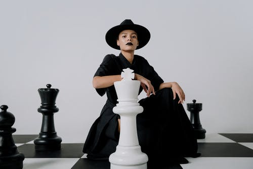 A Woman in a Black Dress and Black Hat Sitting on a Chessboard With Chess Pieces