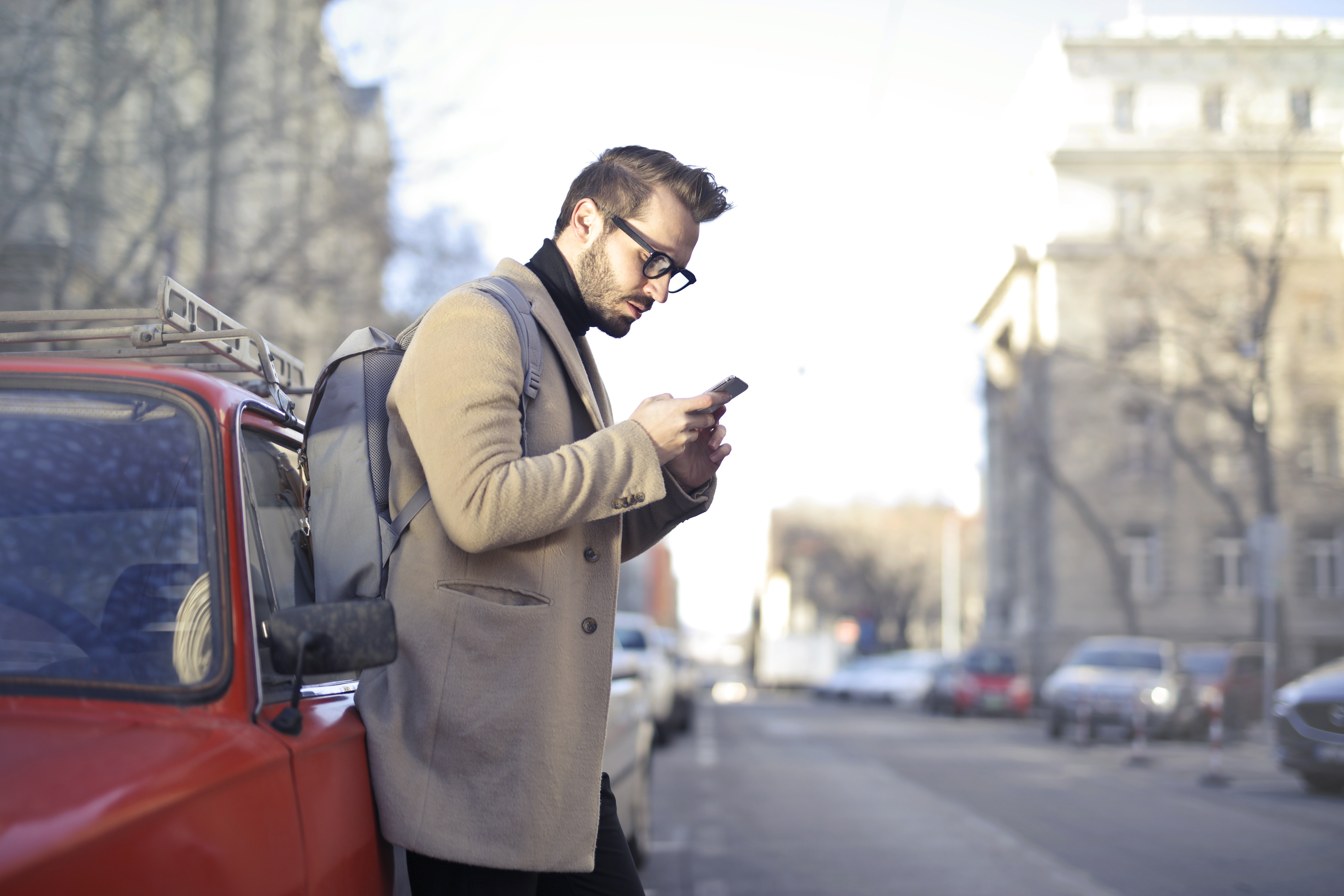 Man in Beige Coat Holding Phone Leaning on Red Vehicle