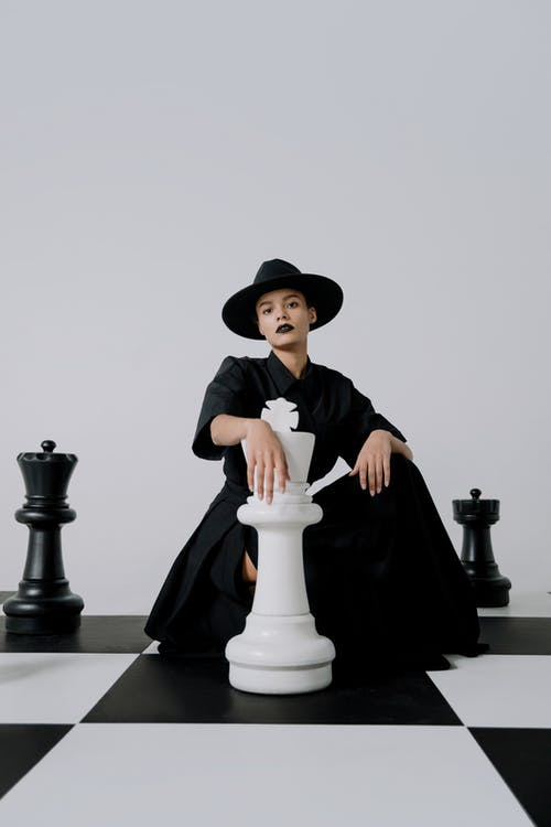Woman in Black and White Long Sleeve Dress Wearing Black Hat Sitting on Black Chair
