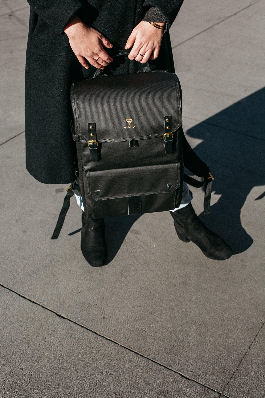 Person Wearing Black Coat Holing Black Leather Knapsack Backpack Standing on Concrete Ground