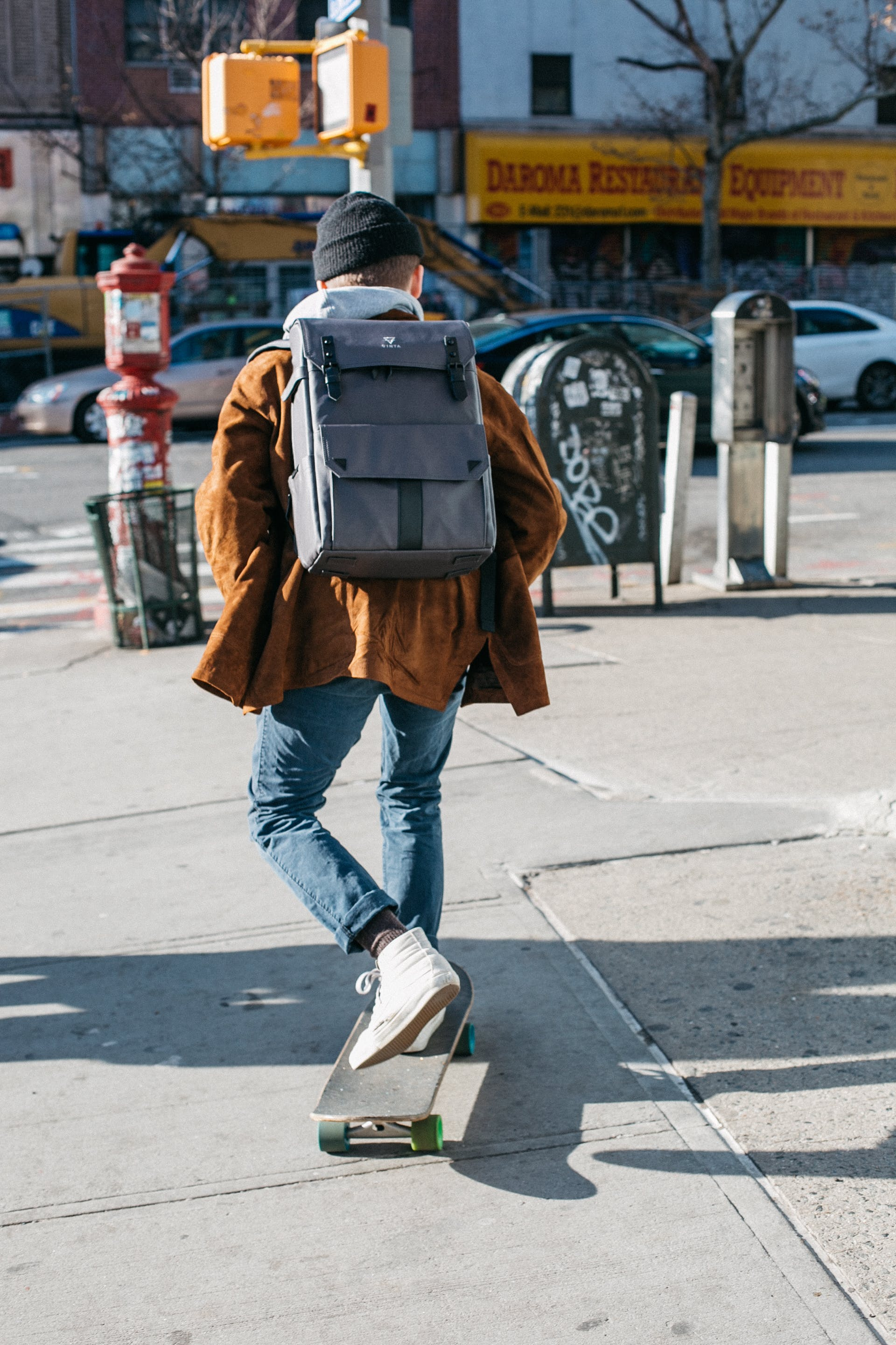 Man Wearing Brown Jacket, Blue Denim Jeans, and White Shoes Riding Skateboard on Sideway