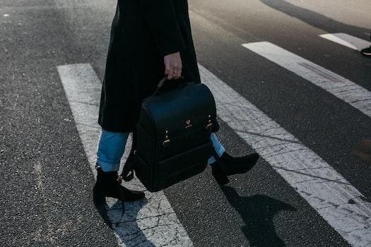 Person Carrying Bag Walking on Pedestrian Lane