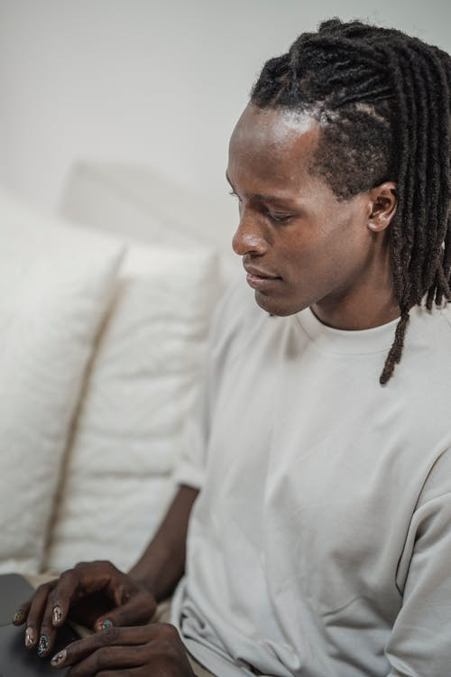 Man in White Crew Neck T-shirt Sitting on White Couch