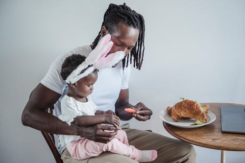 A Father Giving His Child a Piece of Candy