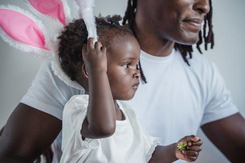 A Child Holding a Bunny Ear Hairband
