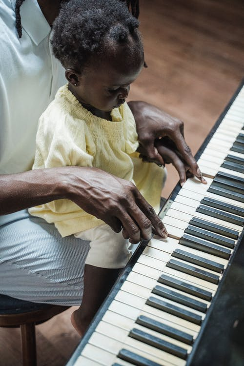 An Adult Teaching a Toddler How to Play the Piano