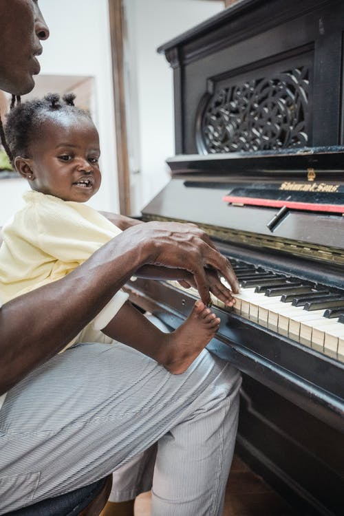 A Man Playing the Piano With His Daughter