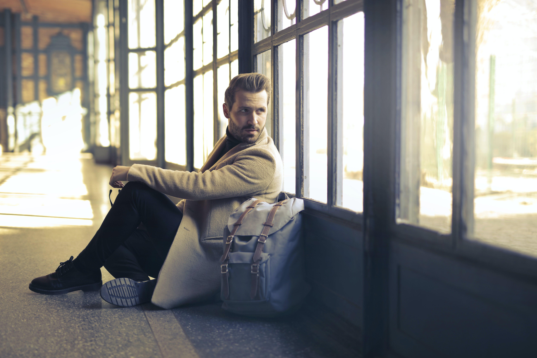 Man Wearing Brown Coat Beside White Backpack Sitting Near Window
