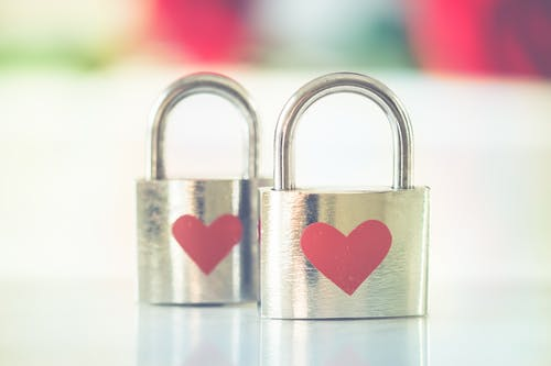 Bokeh Photo of Two Heart-printed Stainless Steel Padlocks