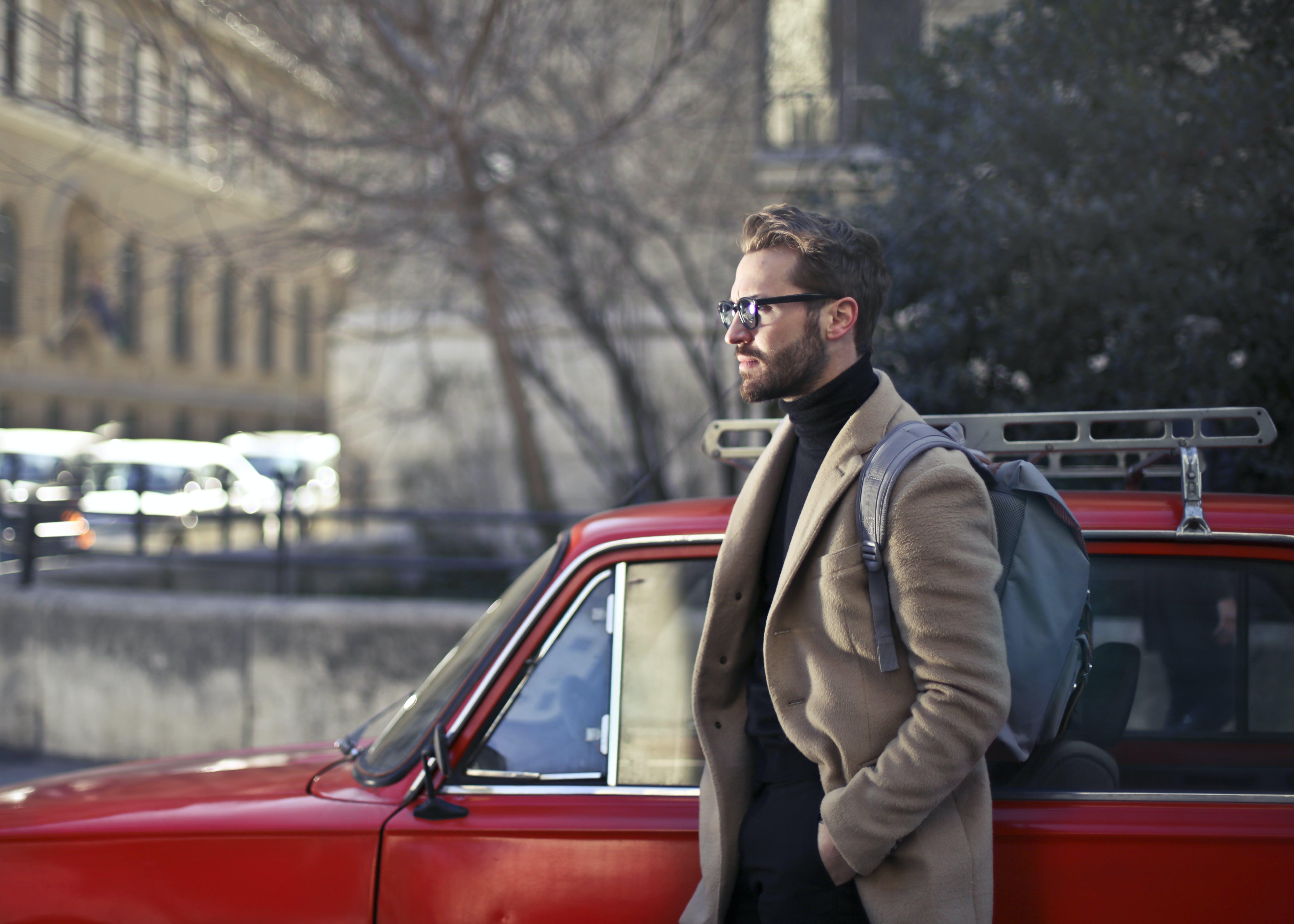 Man Wearing Beige Jacket Beside Red Car
